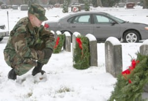 Second Lt. Michael Dunlap from Columbus, currently stationed out of Fort Benning, Ga., places a wreath on the headstone of a soldier.