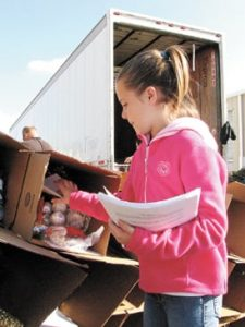 Michaela Graham, a fourth-grader from Frazeysburg, Ohio, answers the call to duty as she adds holiday greetings to Christmas trees being boxed for shipment to military servicemen and women stationed overseas. The culmination of Operation Evergreen took place at the Department of Agriculture in Reynoldsburg on Nov. 13.