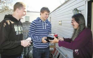 Mitchell Howard (left), a member of West Jefferson High School's student council, and student council president Logan Stepp deliver a meal to West Jefferson resident Michael Tabor during a weekly round of service for Lifecare Alliance's Meals on Wheels program.