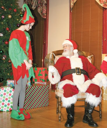 Santa Claus consults with elf Kaitlyn Roush in Groveport Town Hall on Dec. 6 as they await the arrival of children  coming to give Santa their Christmas wish list.