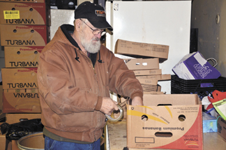 Francis Davis constructs boxes to be filled with food for pantry clients. Davis has volunteered at the pantry for three years.