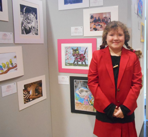 "Photo courtesy of the Department of Education  Alton Hall student Haley Young stands in front of her winning visual arts entry, ""The Cat Who Smells Flowers"" at a national exhibit."