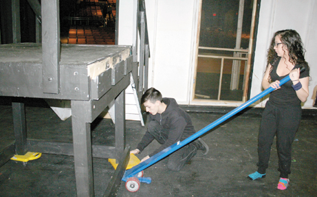 The Cruiser Theatre Troupe's backstage tech crew is not afraid of doing some heavy lifting as Amber Nunez uses a wheeled lever to lift a portable staircase as Cameron Brown places wheels under it so the staircase can be moved and stored backstage.