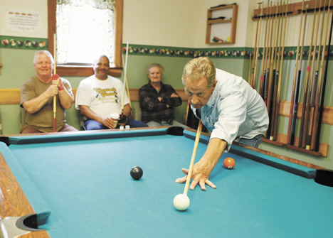 Messenger photo by Mike Munden Bob Hillard lines up a shot during a friendly game of billiards at the Madison County Senior Center in London. Watching are: (from left) William Koerner, Marc Stanley and Bob Estheimer. The group plays in a league, as well as just for fun.