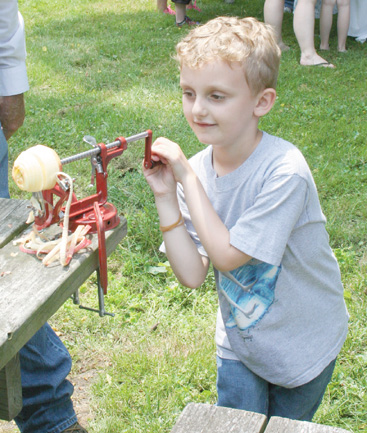 Gabriel Compton tries his hand at peeling and coring apples.