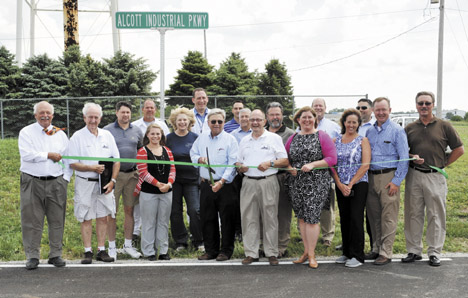 Messenger photos by Jeff Pfeil Businessman Jerry Alcott prepares to cut the ribbon to open the new Alcott Industrial Parkway and Alcott Drive in Mount Sterling. Business representatives and local, county and state officials were on hand for the June 12 ceremony.
