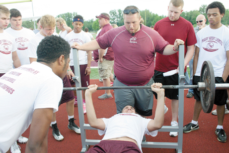 Messenger photos by Rick Palsgrove Canal Winchester High School sophomore and football player Jacob Osborne received encouragement from  his teammates and assistant coach Brent Palsgrove as he did bench presses at the Friday Night Lights football combine event at Canal Winchester High School's Mike Locke Stadium on May 29.