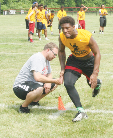Groveport Madison Cruiser football player Rico Richards performs an agility drill at the camp as Cruiser assistant coach Josh Chilcote times his efforts.