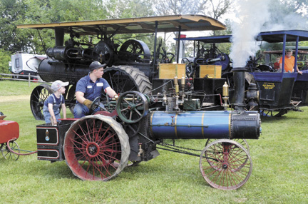 Wyatt Downard of Camden, Ohio, gives Ross Baughman of Nelsonville, Ohio, a ride around Plain City's Pastime Park, site of the Miami Valley Steam Threshers Show. They are headed to the sawmill to cut some wood. The half-scale Case steam engine was built in the 1960s.