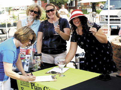 Kerri Ferguson (far left), Plain City village council member and business owner, and Shannon Pine (far right), Plain City resident and Planning and Zoning Committee volunteer,  sign a petition to move the Local Liquor Option to the November ballot. Julie Weaver (middle left) and Mary Brown (middle right) show their support. All are Uptown Plain City Organization volunteers.