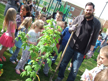 """Messenger photo by Dedra Cordle Christopher Stanley, author of """"The Tree Watcher,"""" helps students at Finland Elementary plant a maple tree on school grounds. Stanley, who grew up in Grove City, visited the school on May 11 to talk about the importance of mindfulness and imagination."""