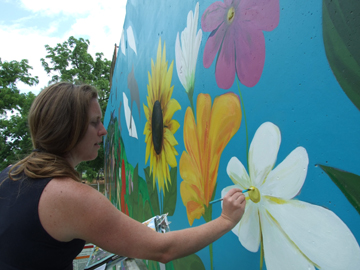 Messenger photo by Dedra Cordle Artist Danielle Poling stands before her mural, The Fantastic Food Garden, at Westgate Park. Poling, who was commissioned by Summer Jam to bring public art to the community, began painting the mural near the racquetball courts in mid-June. A public dedication for the artwork will be held July 12 at 6 p.m. at Westgate Park.
