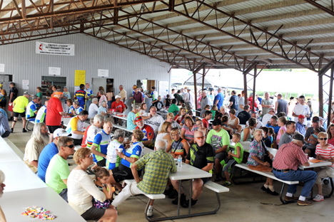 A large crowd gathers under the shelter at Trinity United Methodist Church as a line forms for home cooked food.