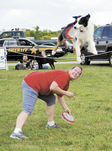 Jetta, the flying dog, jumps over his owner, Megan Brown, to snag a disk during a demonstration by Southern Ohio Flying K9s.