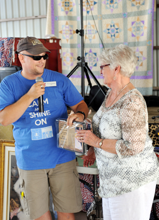 Trinity United Methodist Pastor Jon Osmundson presents a plaque to Carol Gatrell, honoring her and her late husband, Bill, as grand marshals of the Homecoming parade.